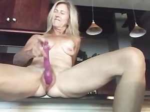 Nude light-haired stretches out her legs massaging pussy with a gigantic fake penis